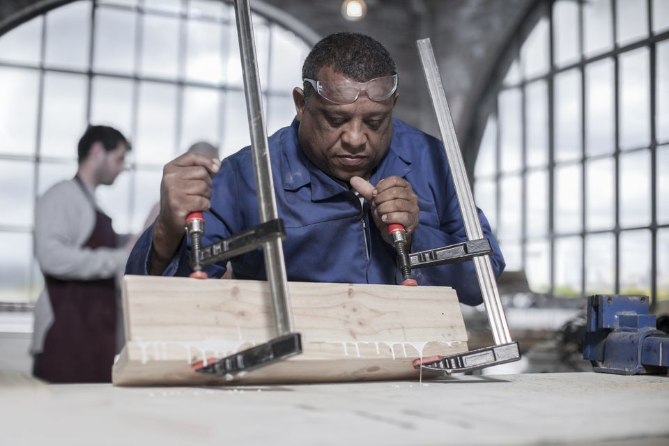 Carpenter using clamps to glue wood