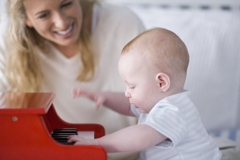Mother watching baby boy (5-8 months) play piano (focus on baby)