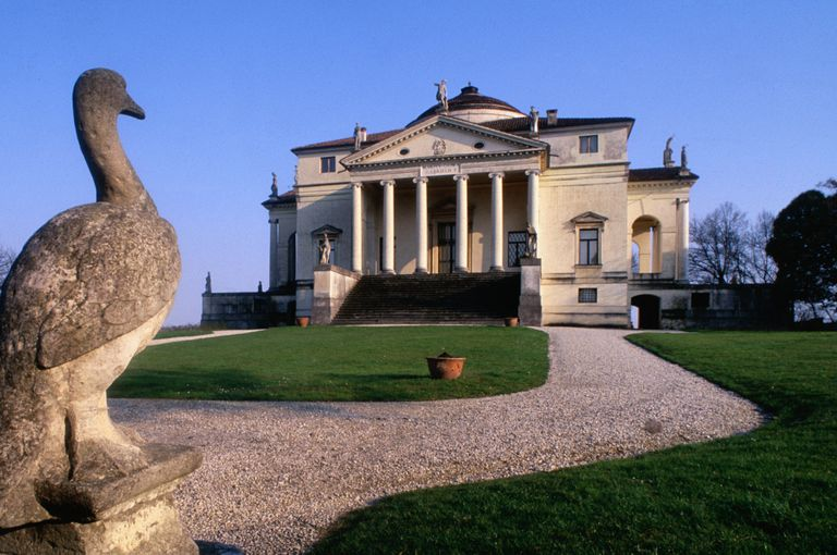 Palladio-designed villa with pediment, columns, and dome in a country setting with a bird sculpture in the foreground