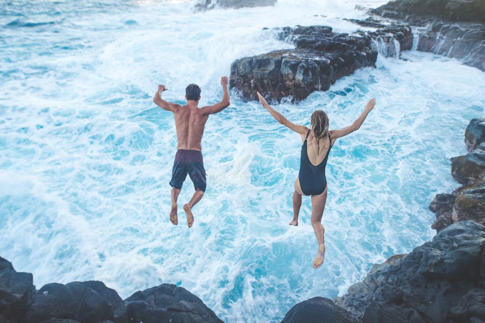 Beautiful couple jumping off cliff into ocean