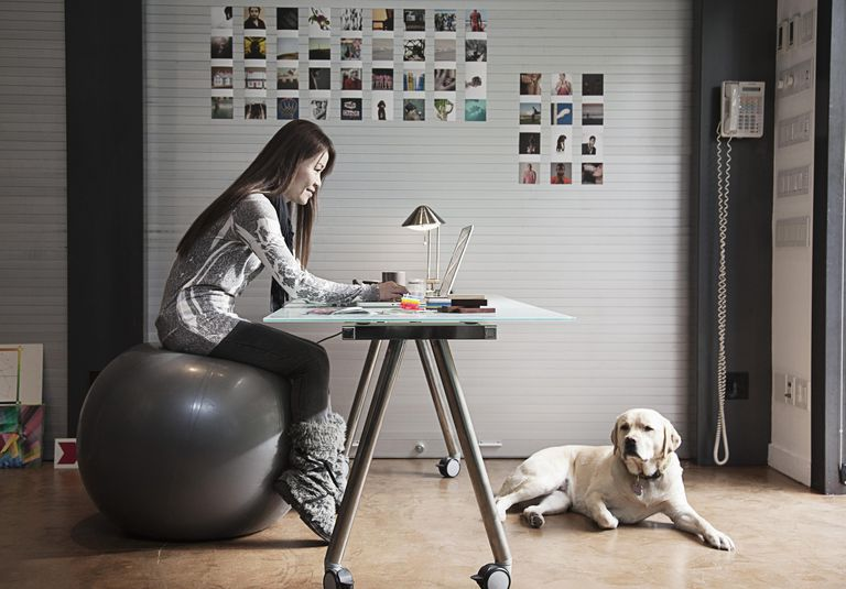 Japanese businesswoman sitting on exercise ball and working at desk