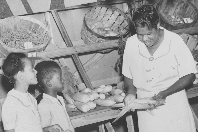 Nannie Helen Burroughs and children at farm stand conneced with her training school for women and girls