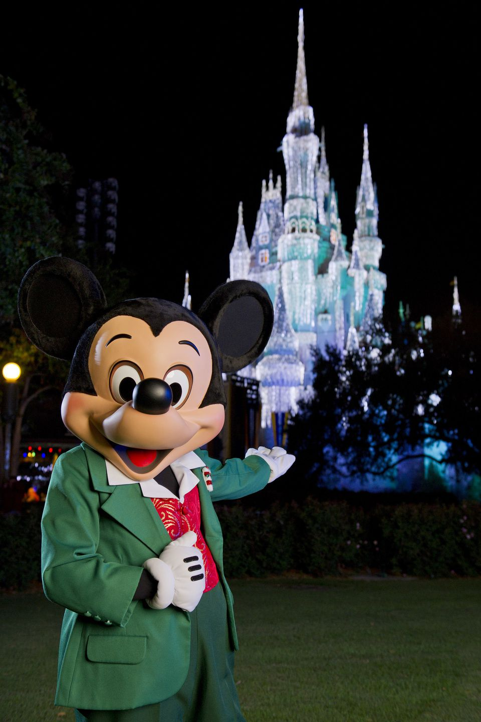 Mickey Mouse dressed for the holidays in front of lighted Cinderella's Castle at Disney's Magic Kingdom.