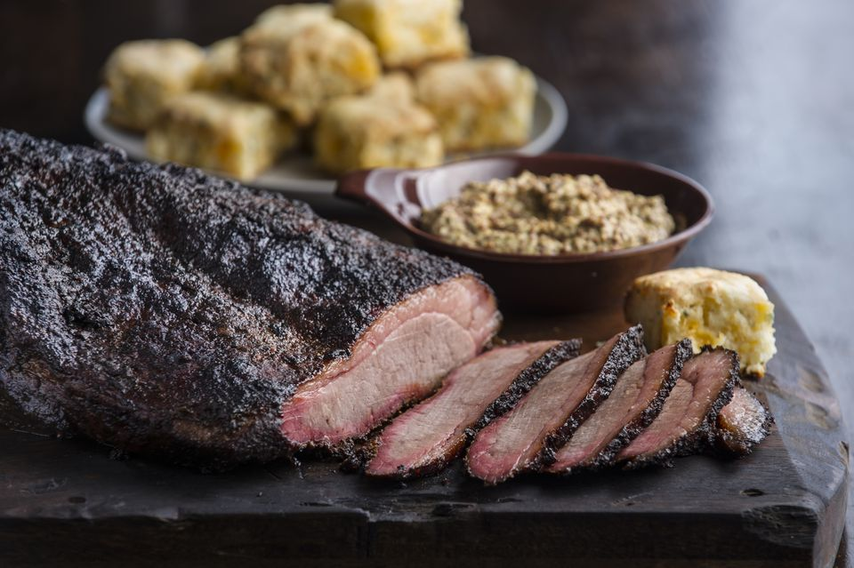 Sliced brisket and biscuits on cutting board