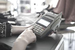Woman using credit card terminal