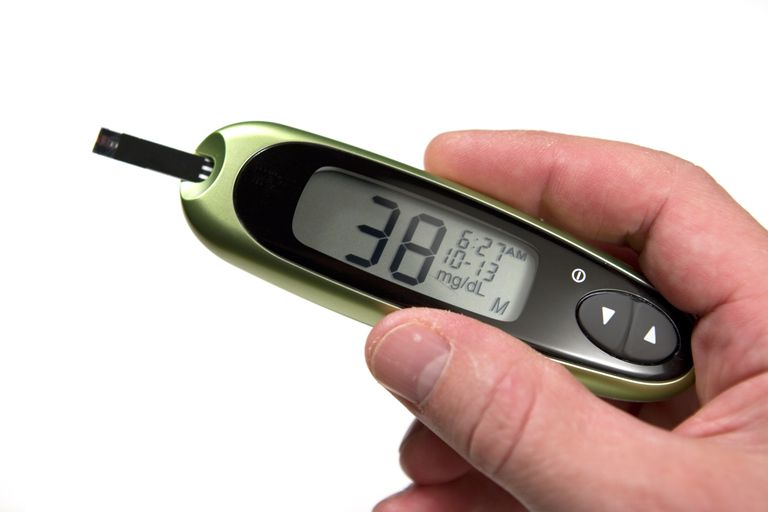 Glucose monitor displaying 38mg/dL being held by a person