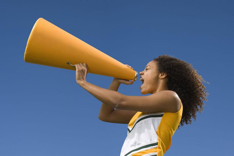 Female cheerleader shouting into megaphon