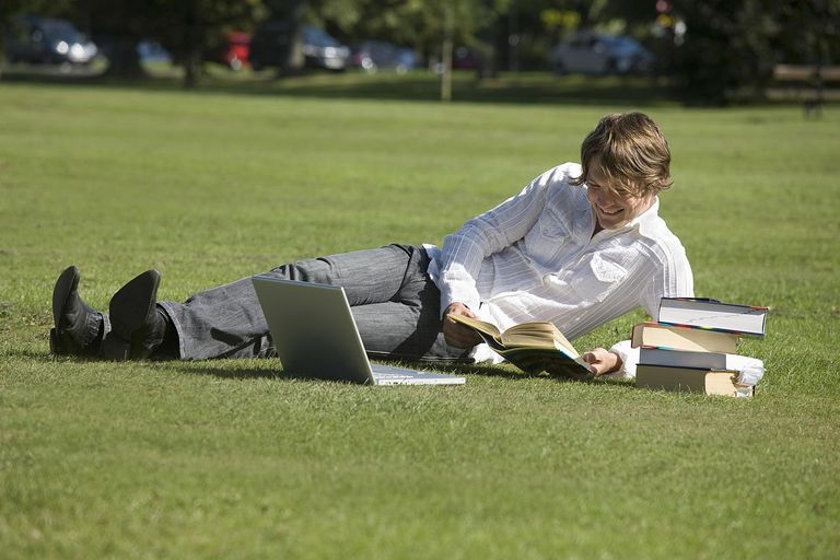 Young man revising with books and laptop i...