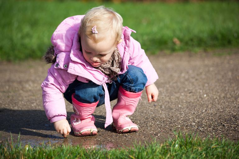 Blond toddler crouching outdoors