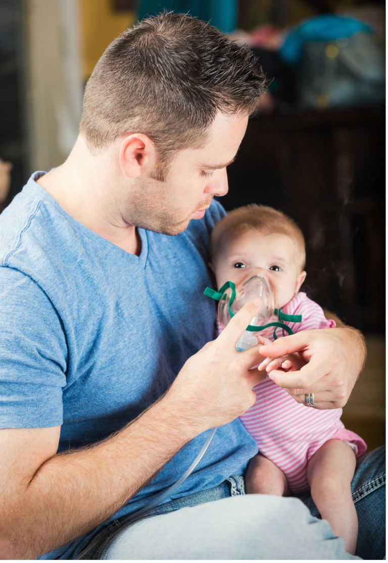 Father giving infant daughter breathing treatment for CF
