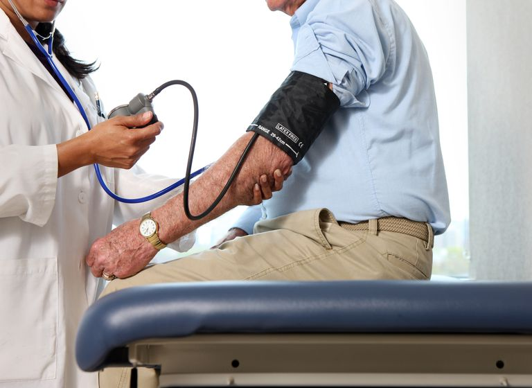 Doctor checks man's blood pressure.