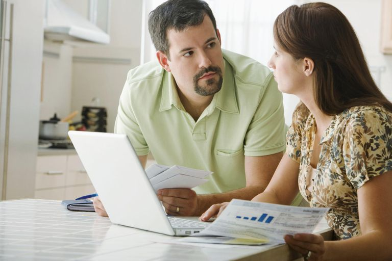 Mid adult couple checking bills in kitchen