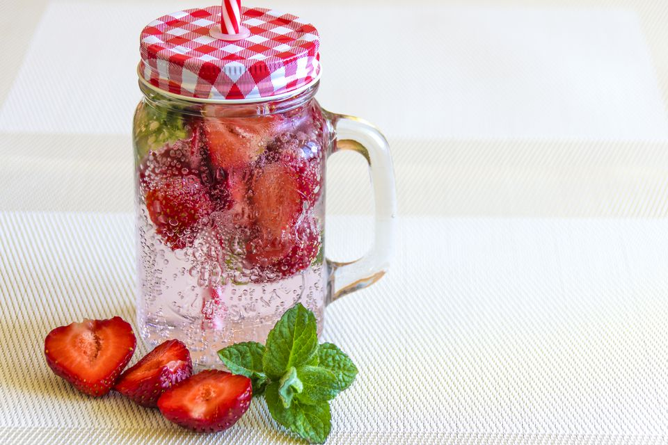 natural soda with strawberries in mason jar
