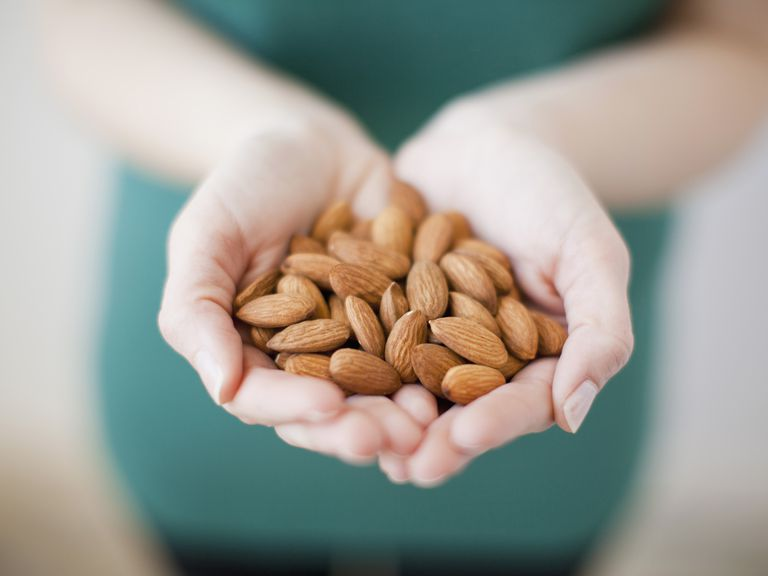 Studio shot of woman showing handful of almonds