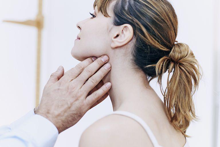 doctor feeling woman's lymph node in neck