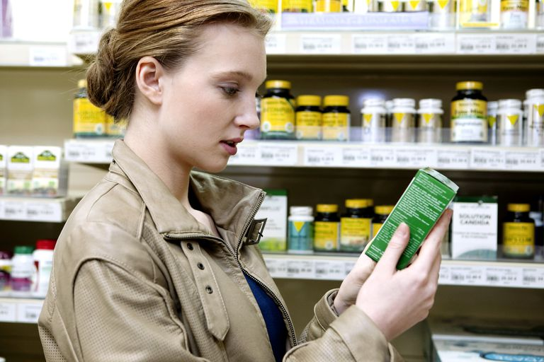 woman at health food store choosing a supplement