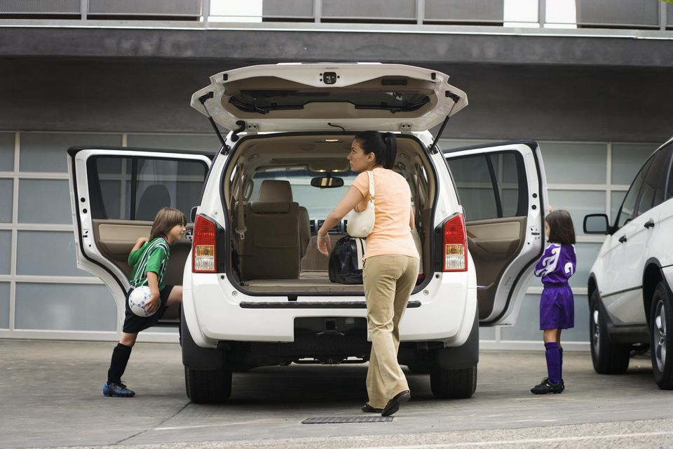 A picture of a woman taking her kids to sports activities