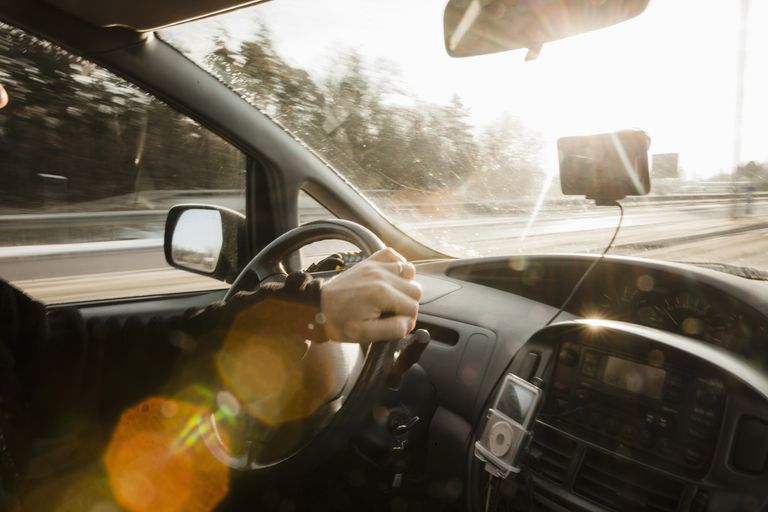 Cropped image of man driving car on sunny day