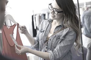 Woman looking at price tag on tank top