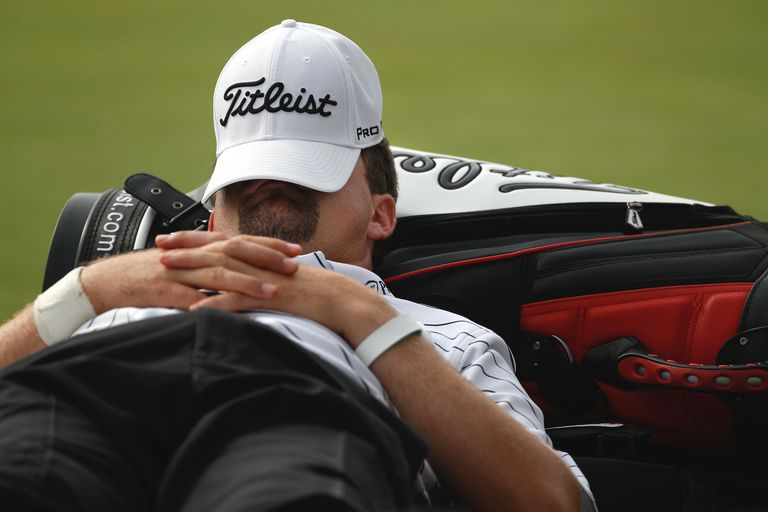 A golfer laying down for a rest due to slow play