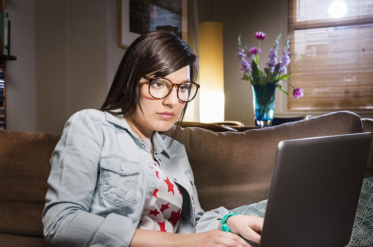 Woman working on laptop at home at night.