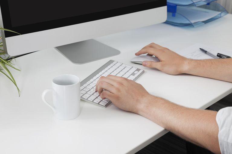 Businessman's hands using computer at desk