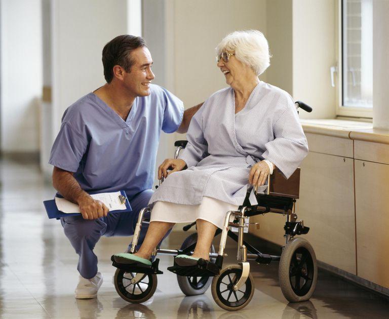 Male nurse talking to elderly patient in wheelchair