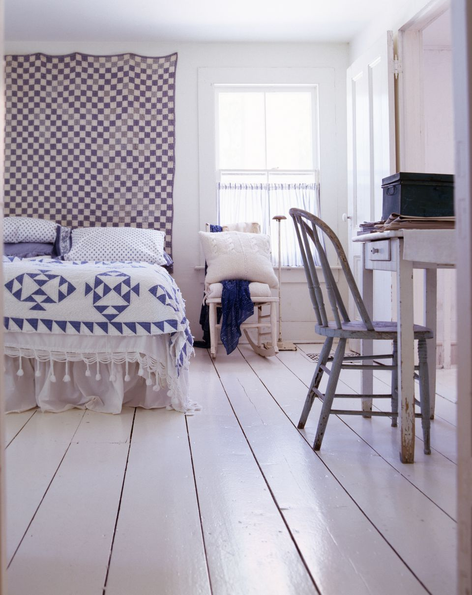 White and blue country bedroom with quilted wall hanging