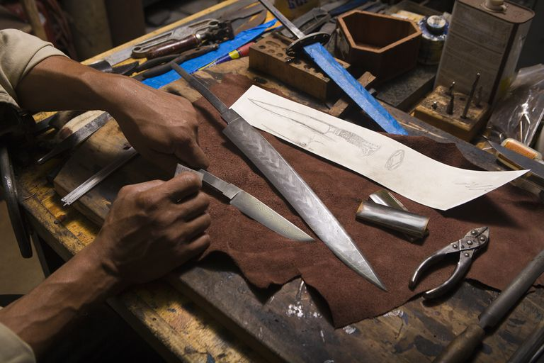 Modern knifemaker polishing a Damascus steel blade