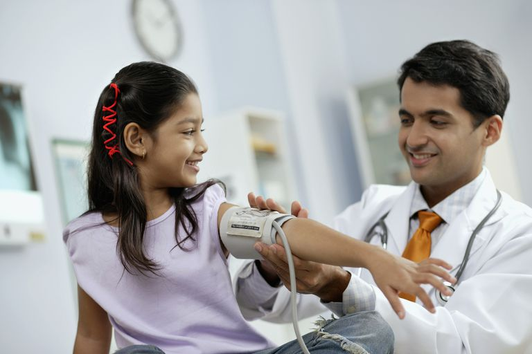Doctor taking girl's blood pressure