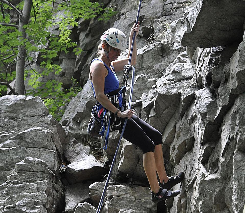 abseiling or rappelling down a rock face