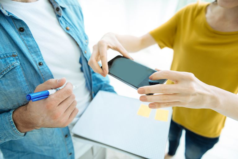 Woman scanning man's notebook with smartphone