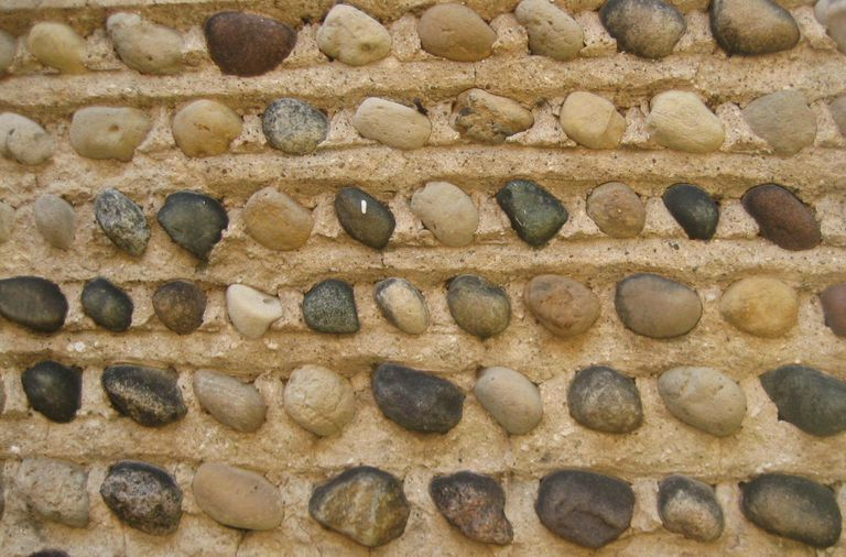 close-up of house siding, large horizontal grooves with stones inlaid