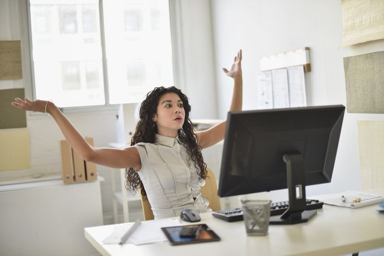 Angry woman sitting at her desk with hands in the air