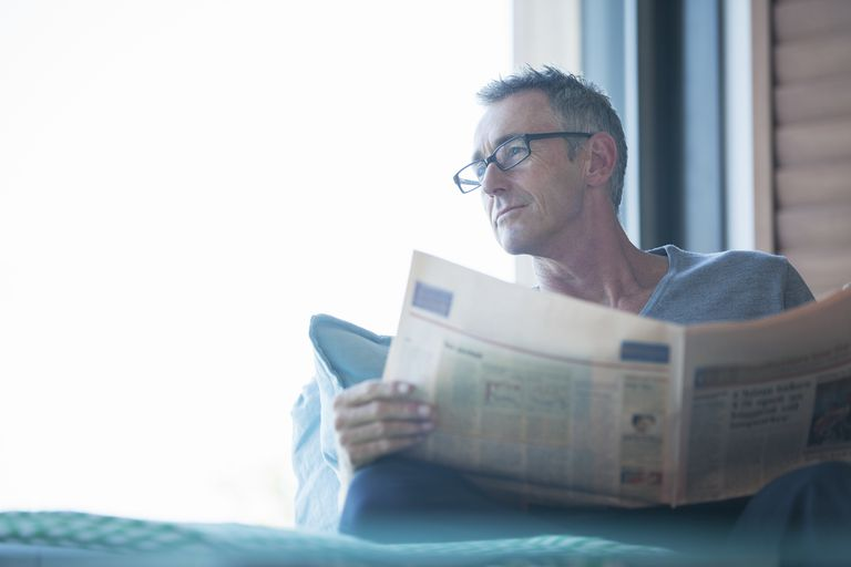 Close up of man reading newspaper in living room