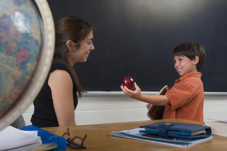 Boy (6-8) in classroom giving female teacher apple, smiling, side view
