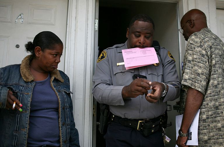African American police officer giving eviction notice to African American man and woman