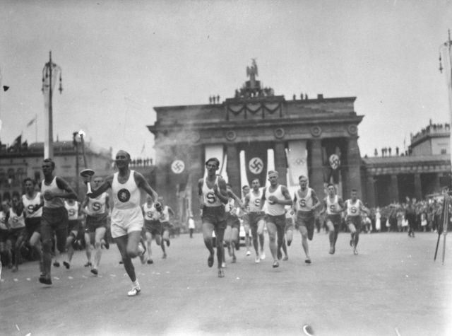 Olympic torch bearer running through Berlin for the 1936 Nazi Olympics.