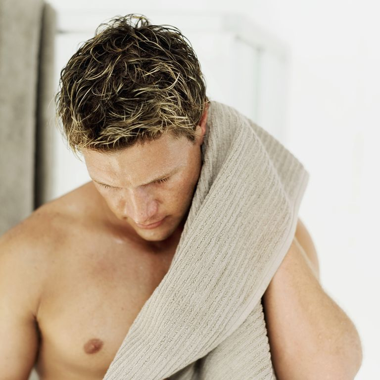 Close-up of a young man wiping himself with a towel