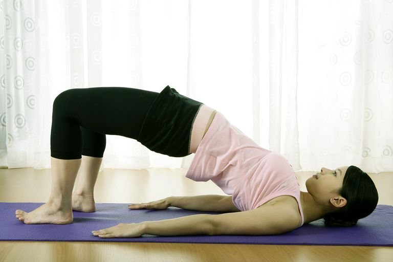 Young woman arching back on yoga mat, side view