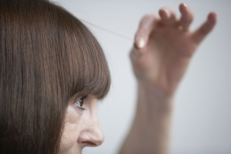 Woman pulling strand of hair
