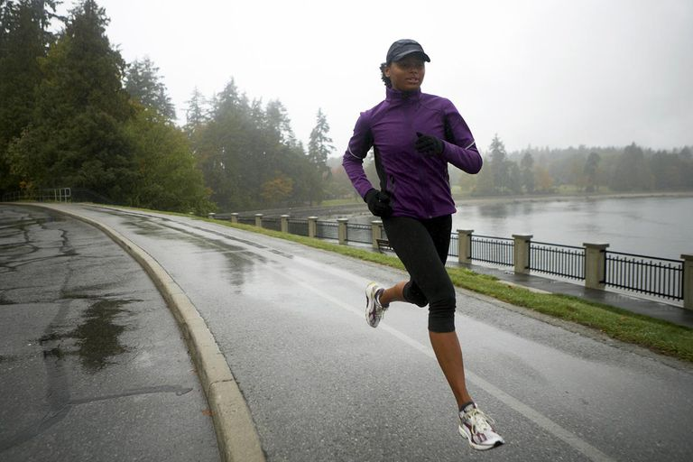 Woman running along waterfront path in the rain