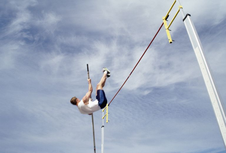 A male pole vault athlete hoists himself through the air to clear the bar.