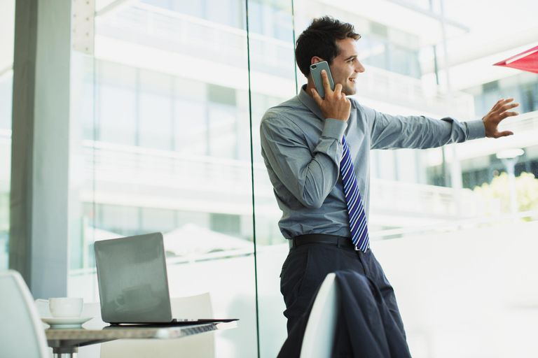 Businessman talking on cell phone at window