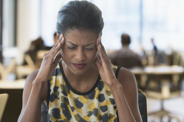 Anxious mixed race businesswoman rubbing temples in office
