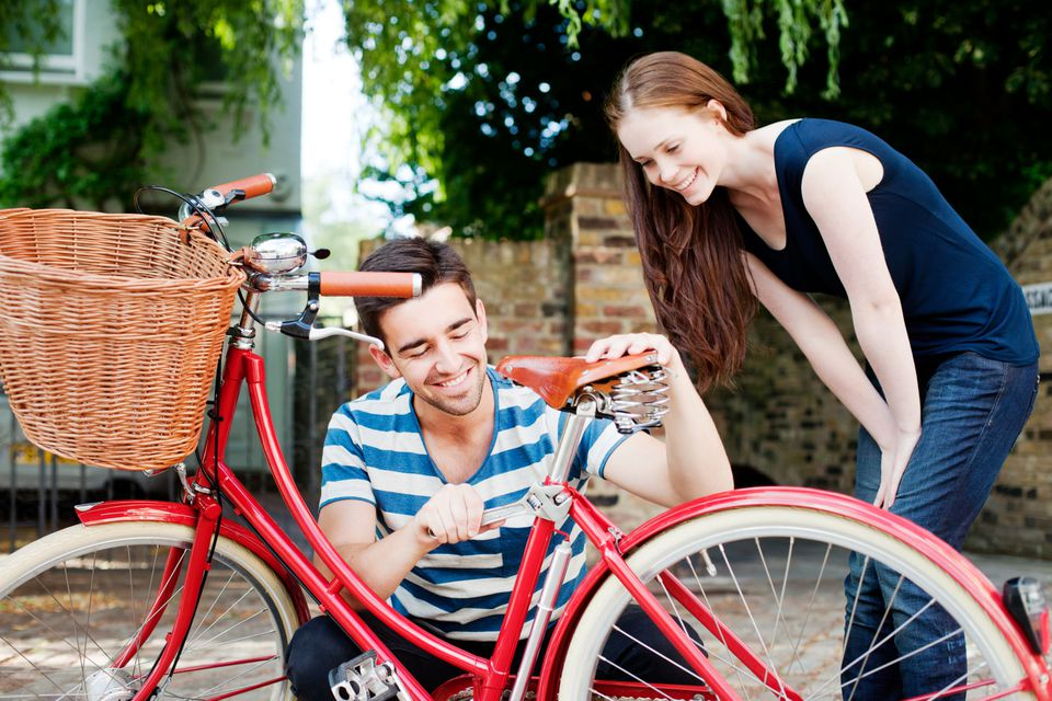 Man helping a woman fix her bicycle