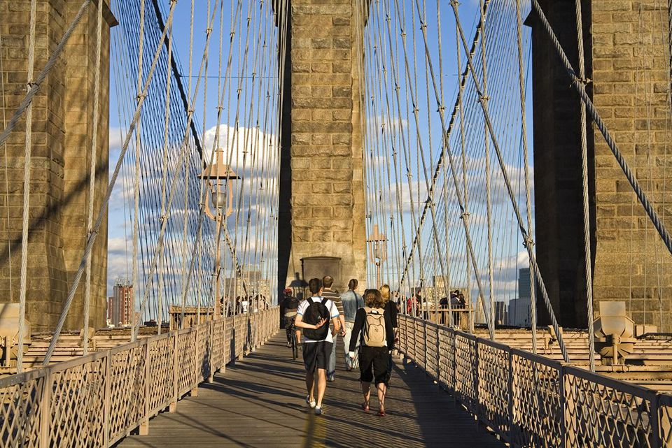 People walking across the Brooklyn Bridge, Manhattan.
