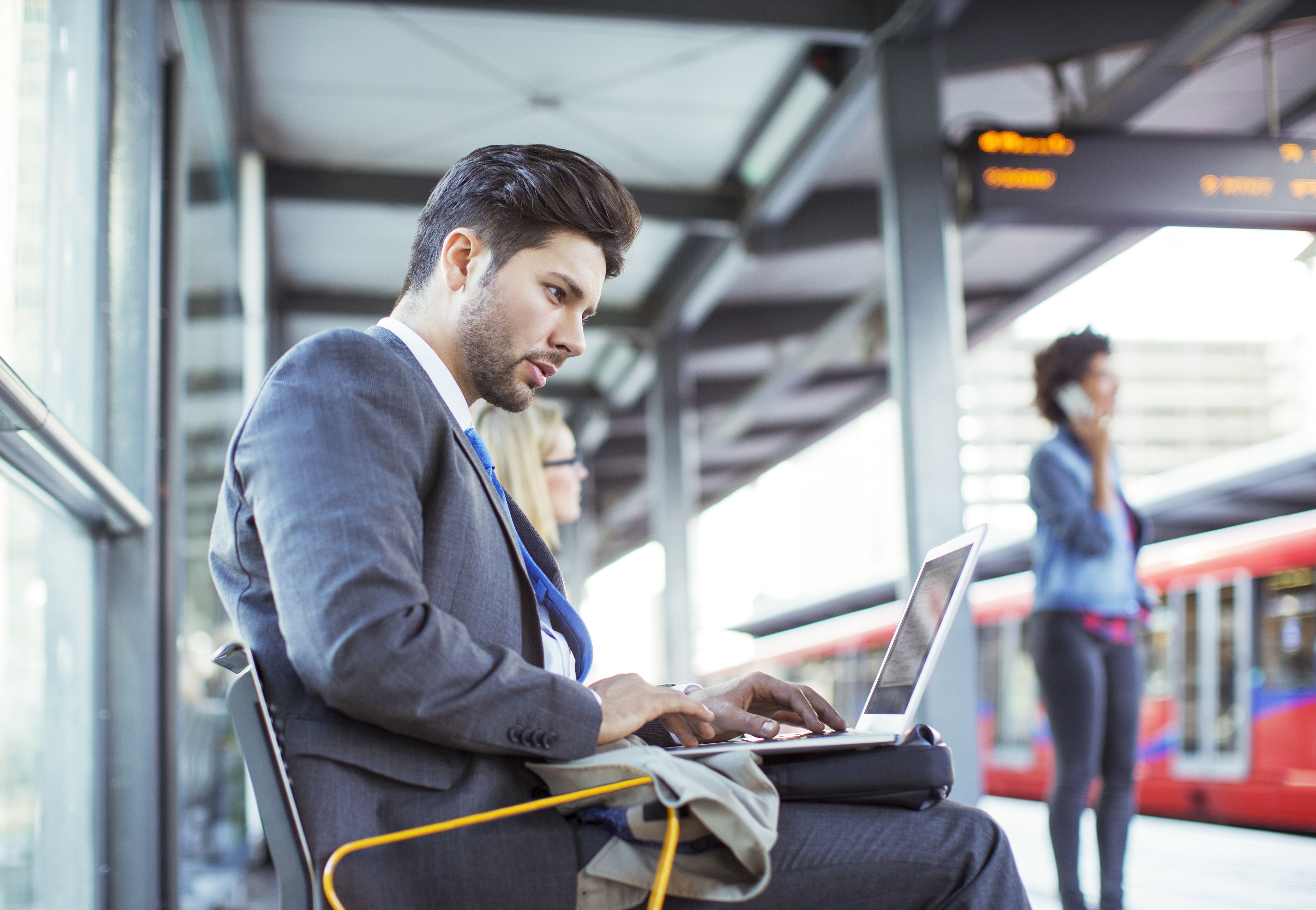 How to mention relocation in a cover letter businessman using laptop at train station madrichimfo Image collections