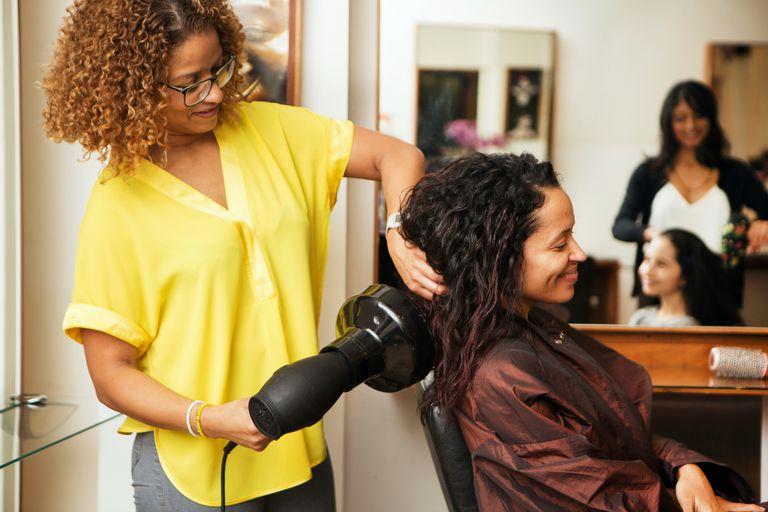 Hair stylist blow drying female customers hair in hair salon