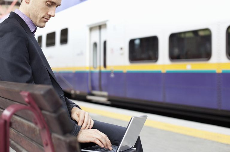 Businessman at train station using laptop